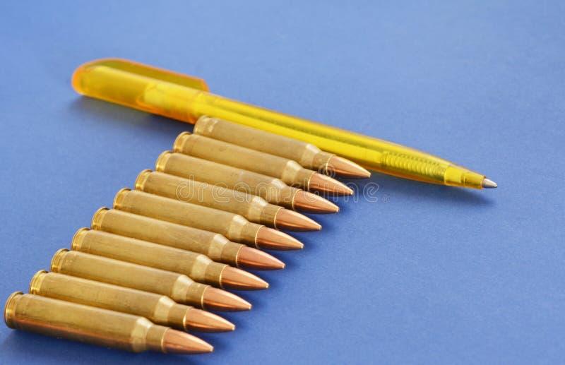 Cartucce militari 5 munizioni di 56mm con la penna come concetto di propaganda nel mass media fotografia stock libera da diritti