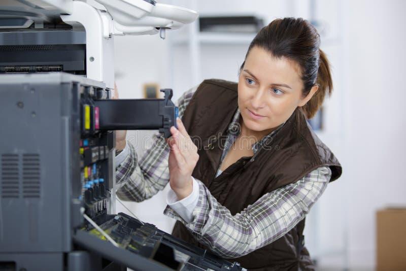 Cartucho de la fijación de la mujer en máquina de la impresora en la oficina foto de archivo libre de regalías