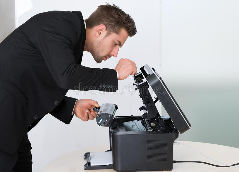 Cartucho novo da fixação do homem de negócios na máquina de fotocópia fotos de stock royalty free