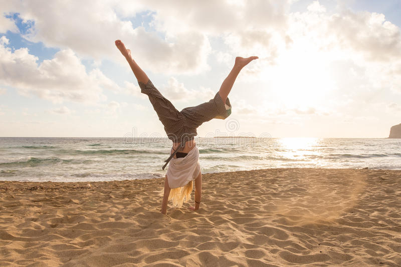 Cartwheel de torneado de la mujer feliz libre que disfruta de puesta del sol en Sandy Beach fotos de archivo
