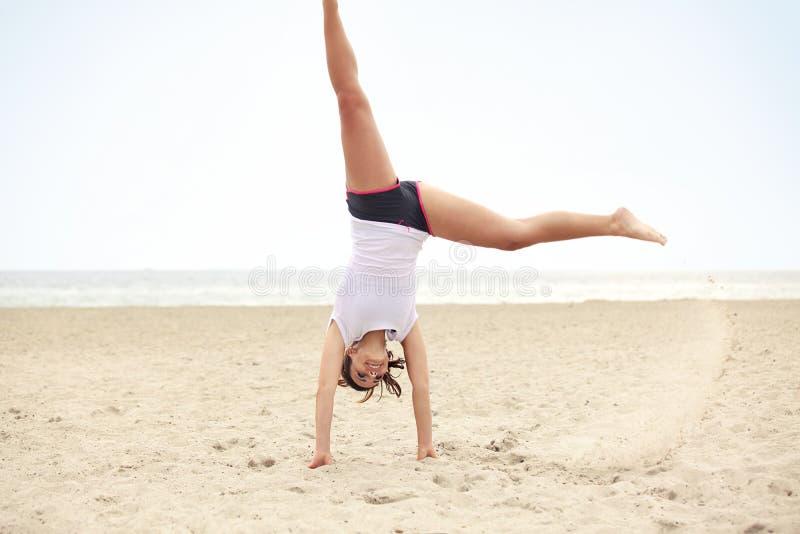 Cartwheel facente femminile felice sulla spiaggia fotografia stock libera da diritti