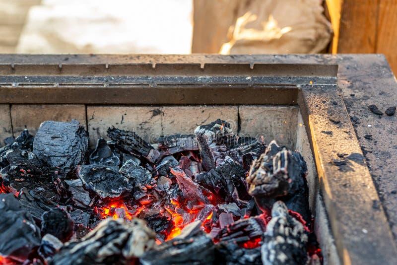 Carvão ardente no soldador do ferro preparação para o assado Chaminé com brasas alaranjadas fotografia de stock