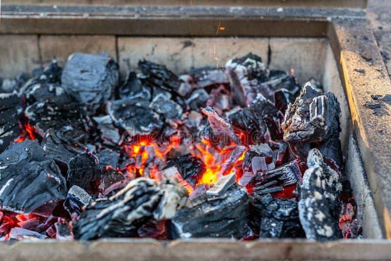 Carvão ardente no soldador do ferro preparação para o assado Chaminé com brasas alaranjadas foto de stock