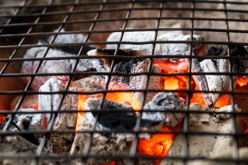 Carvão vegetal ardente com a chama no fogão da argila com o gri do metal fotografia de stock royalty free