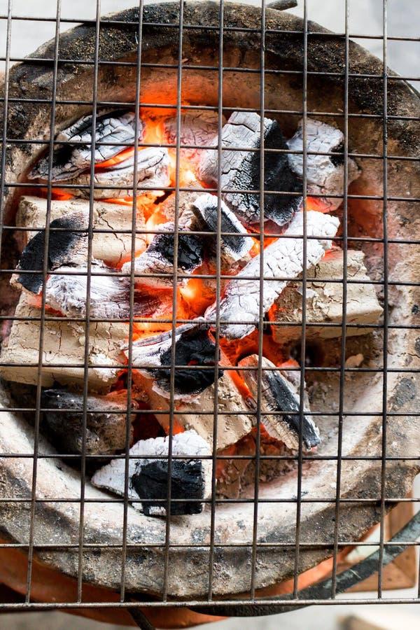 Carvão vegetal ardente com a chama no fogão da argila com o gri do metal foto de stock royalty free