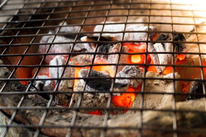 Carvão vegetal ardente com a chama no fogão da argila com o gri do metal fotos de stock