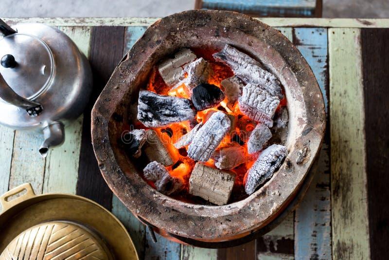 Carvão vegetal ardente com a chama no fogão na tabela imagens de stock royalty free