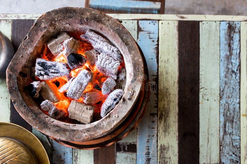 Carvão vegetal ardente com a chama no fogão na tabela imagens de stock