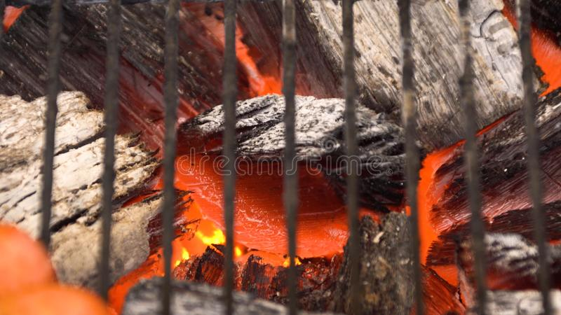 Carvão vegetal quente de incandescência na grade Pit With Flames do BBQ, close-up Os carvões ardentes fecham-se acima imagens de stock