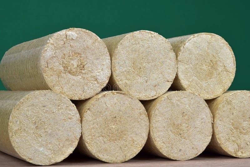 Carvões amassados de madeira endireitados, fundo verde da serragem Combustível alternativo, bio combustível fotografia de stock