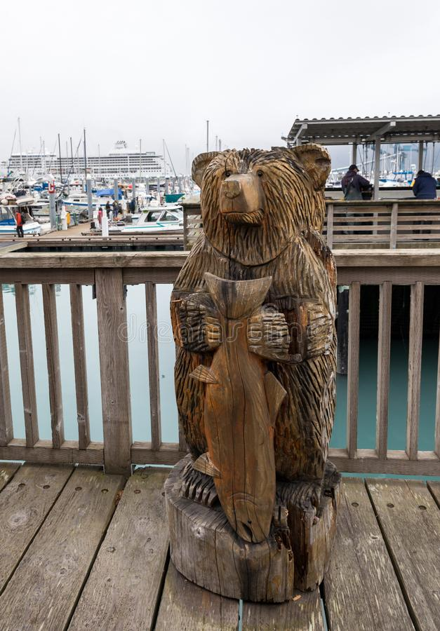 A carved bear holding a salmon on the boardwalk at the small boat harbour at Seward, Alaska with boats and cruise ship in stock photo