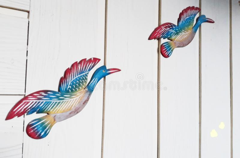 Carved Bird Painted, Mounted on Cream Painted Wall royalty free stock photo