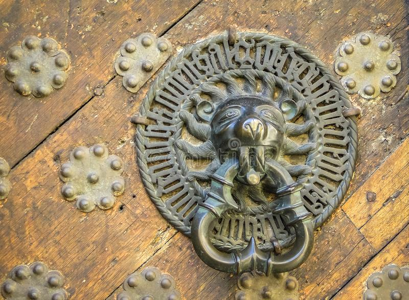 Carved door handle shaped as lion on old wooden door royalty free stock photos