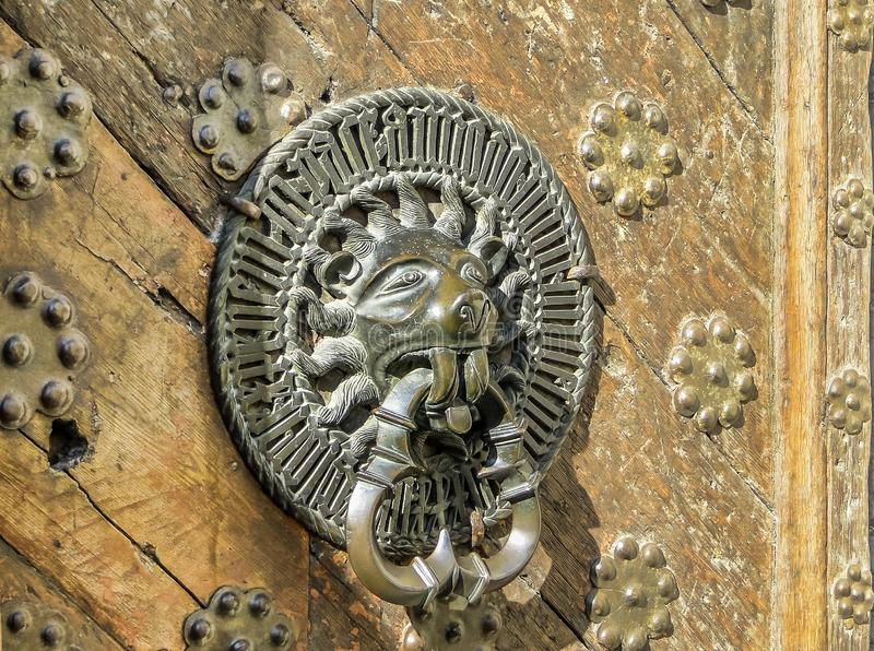 Carved door handle shaped as lion on old wooden door. Carved brass door handle shaped as lion on old wooden door in Tallinn, Estonia royalty free stock photography