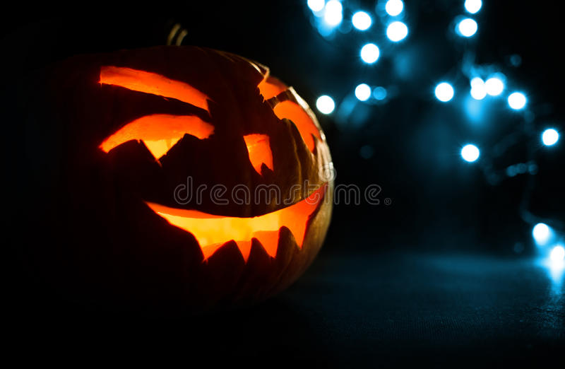 Carved face of pumpkin glowing on Halloween on blue bokeh light background royalty free stock photography