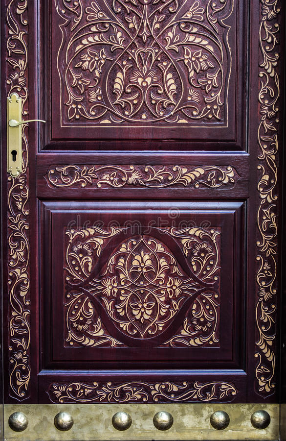 Carved gilded door with brass details and handle.  stock photos