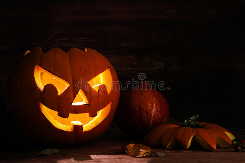 Carved halloween pumpkin with a scary glowing face on dark rustic wood as an autumn decoration, copy space royalty free stock images
