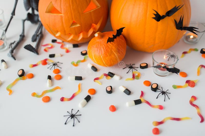 Carved halloween pumpkins and candies stock images