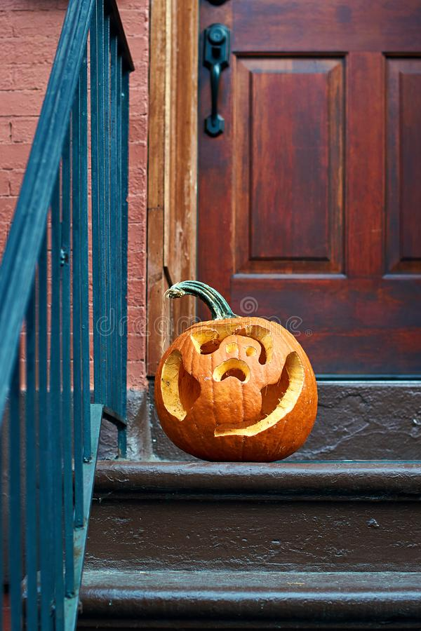 Carved Halloween pumpkins or jack o`lantern on the doorstep in Brooklyn royalty free stock photography