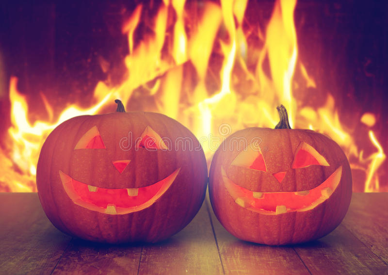 Carved halloween pumpkins on table over fire royalty free stock photo