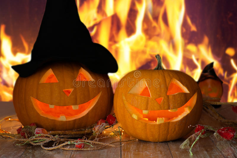 Carved halloween pumpkins on table over fire royalty free stock image