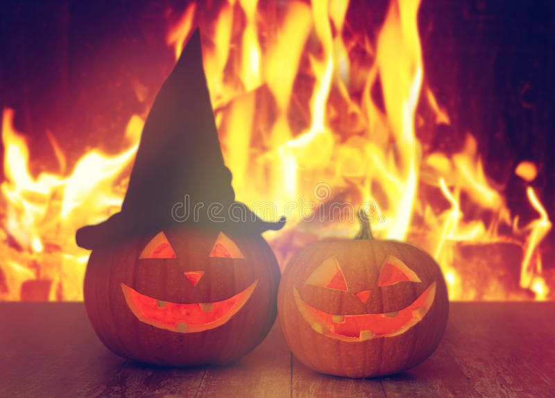 Carved halloween pumpkins on table over fire stock image
