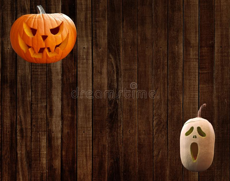 Carved halloween pumpkins on a wall with wooden planks background royalty free stock photography
