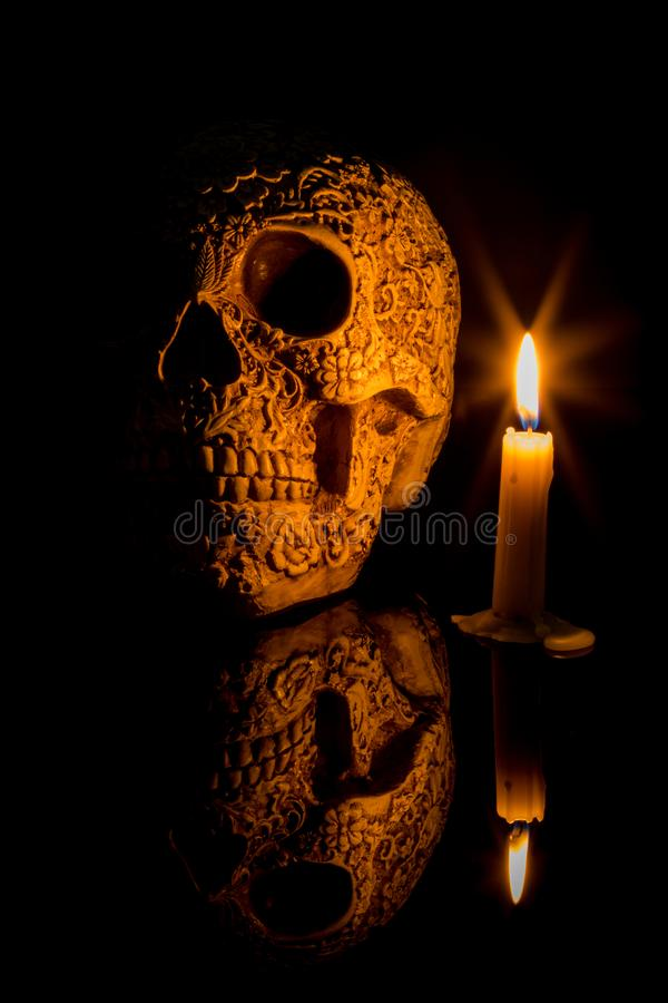 Carved human scull in one candle light in moments of reflection. Carved human scull in one candle light in moments of reflection how much time represented by stock image