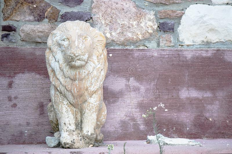 Carved lion statue on the roadside. Patterned wall behind royalty free stock photography