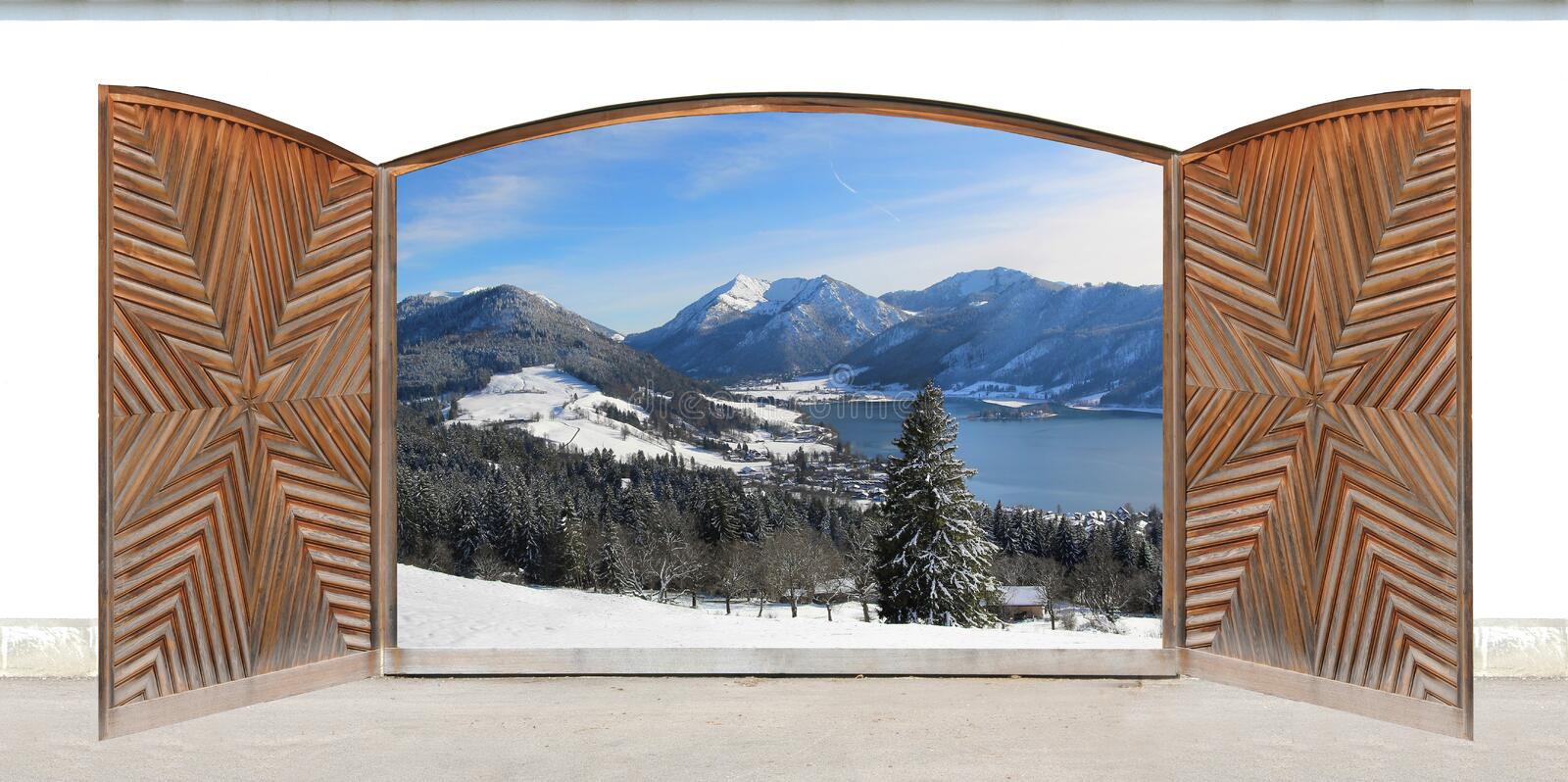 Carved open double door with view to lake and the alps. Carved open double door with wintry lake view and mountains, german winter wonderland royalty free stock image