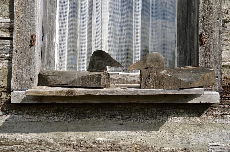 Carved primitive wooden duck decoys. A pair of carved wooden duck decoys rest on a ledge of a log cabin window. (black and white royalty free stock photo