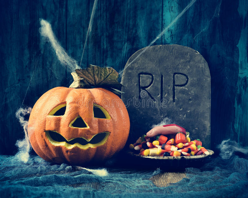 Carved pumpkin, gravestone and Halloween candies. A plate with Halloween candies and an amputated finger in a dismal scene with a carved pumpkin and a gravestone royalty free stock photography