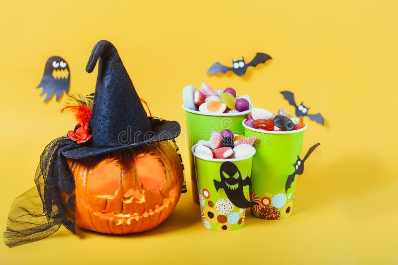 Carved pumpkin in hat and paper cups with sweets, candies decorated with silhouettes of bats, witch, ghosts on yellow background. Spooky holiday symbols royalty free stock photos