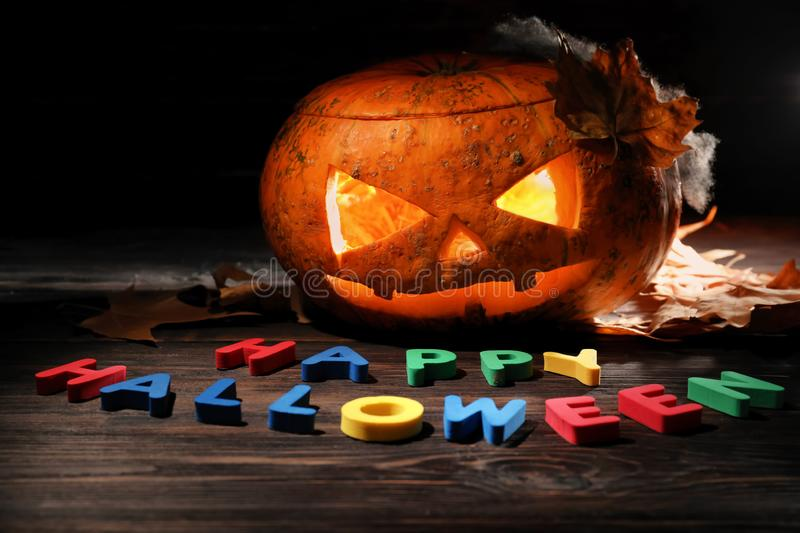 Carved pumpkin and letters forming text HAPPY HALLOWEEN on wooden table in darkness royalty free stock image