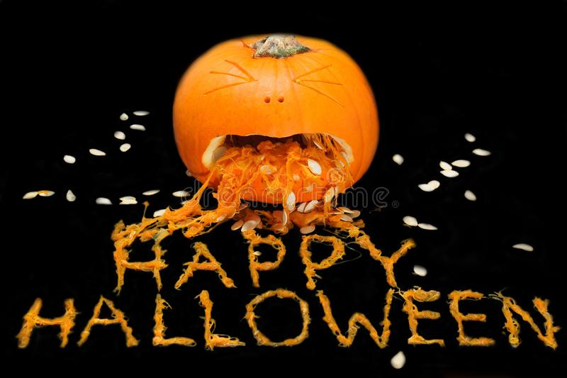 A carved pumpkin with HAPPY HALLOWEEN spelled out with the pulp. A carved pumpkin looks to be vomitting the phrase HAPPY HALLOWEEN from the pulp royalty free stock photo