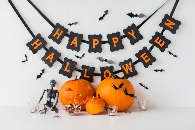 Carved pumpkins with candies and halloween garland stock photos