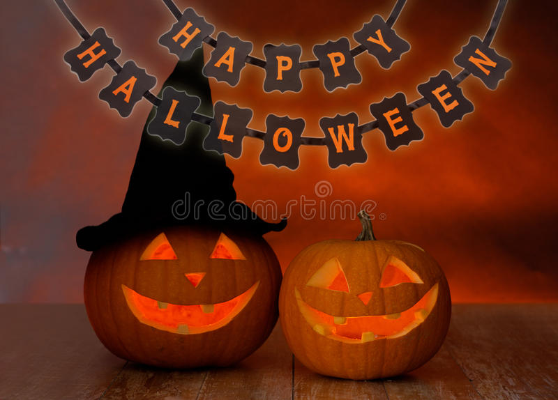 Carved pumpkins and happy halloween garland. Holidays, decoration and celebration concept - jack-o-lanterns or pumpkins in witch hat and happy halloween festive stock images