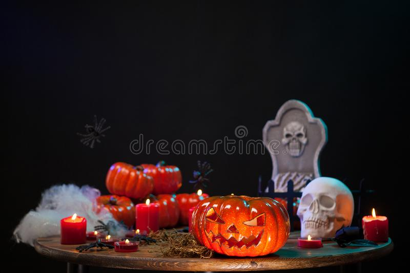Carved scary pumpking sitting on a wooden table with a creepy skull at halloween celebration stock photo