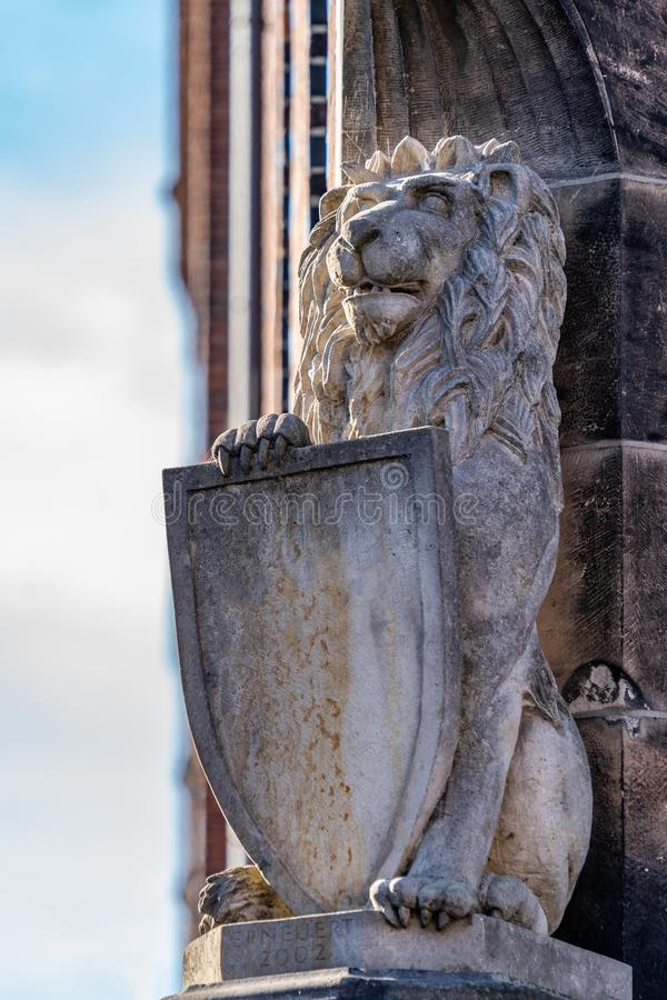 Carved stone lion with heraldic shield. Carved stone lion with heraldic shield on the exterior facade of a historic brick building with a view to a cloudy blue royalty free stock photo