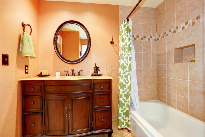 Carved wood bathroom vanity cabinet with mirror. Warm bathroom interior. View of carved wood bathroom vanity cabinet with oval mirror royalty free stock photos
