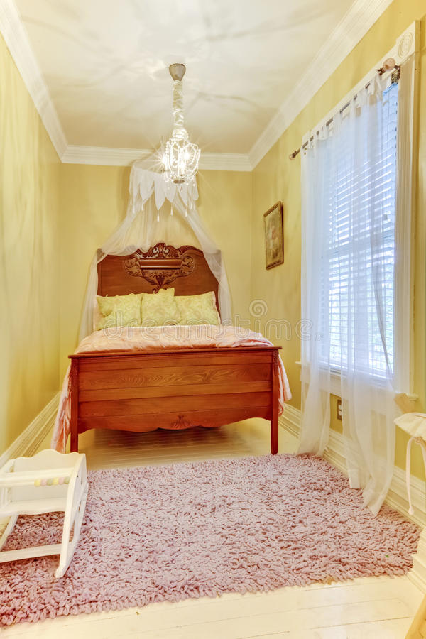 Carved wood bed with pillows in small yellow bedroom. Carved wood bed with pillows in small yellow bedroom with pink rug stock image