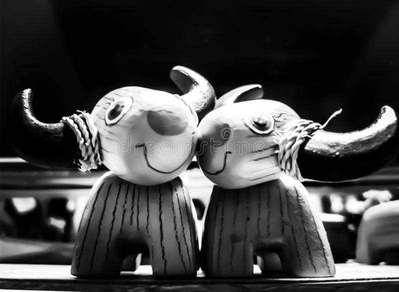 Carved wood buffalo loved each other black and white tones. royalty free stock photos