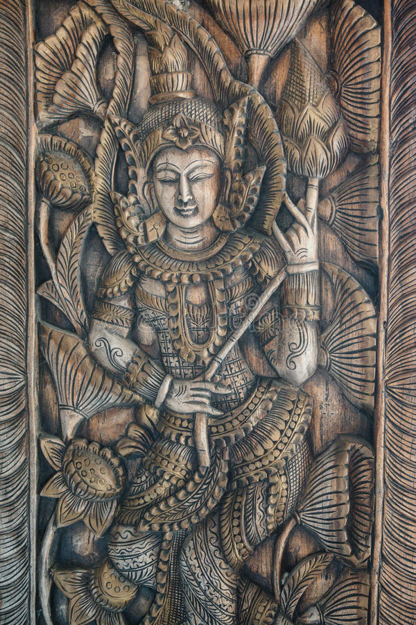 The carved wood that is a shape of human and lotus. royalty free stock photos