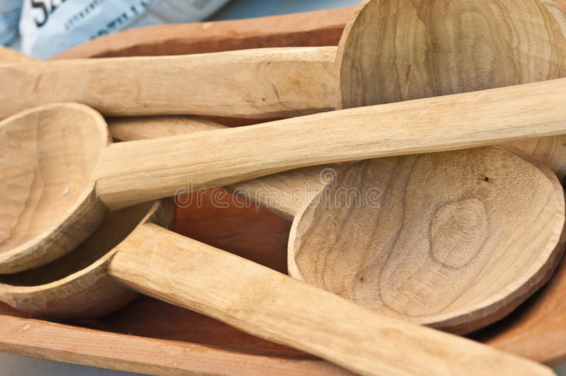 Carved wood spoons. Bowl of carved wood spoons, for sale at an open air, tropical farmers market stock image