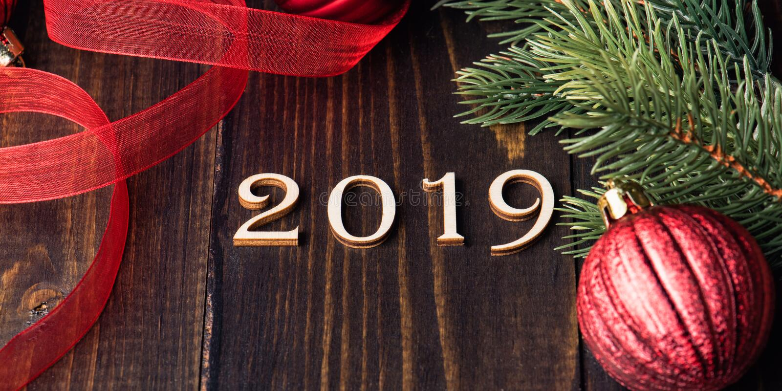 Carved wooden digits forming number 2019 on wooden background. With fir-tree branches and red ribbon and Christmas tree ornaments. New Year symbol, top view stock images