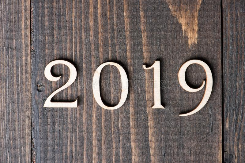 Carved wooden digits forming number 2019 on wooden background. New Year symbol, top view royalty free stock photography