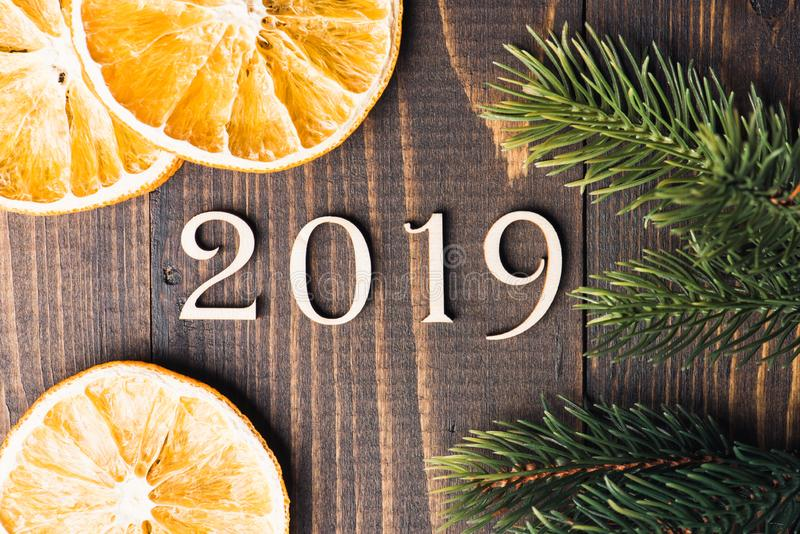 Carved wooden digits forming number 2019 on wooden background. With oranges and fir-tree branches. New Year symbol, top view stock photography