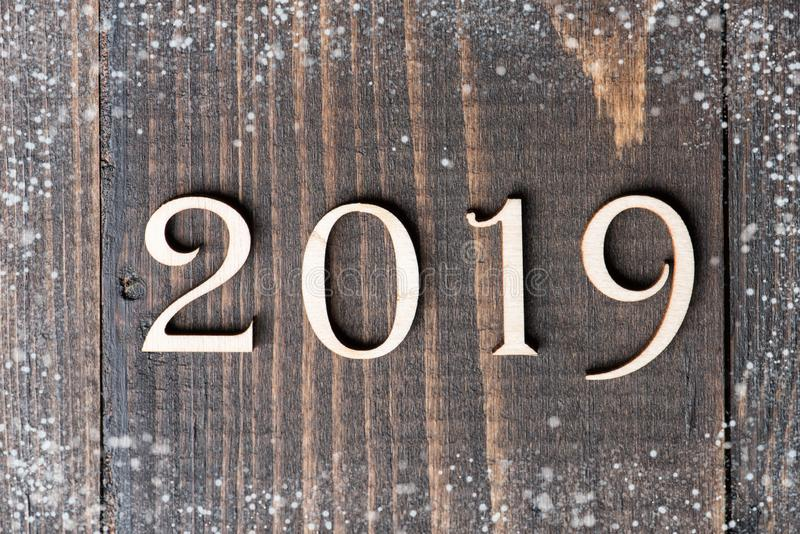 Carved wooden digits forming number 2019 on wooden background. With snow. New Year symbol, top view stock photos