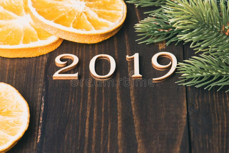 Carved wooden digits forming number 2019 on wooden background. With oranges and fir-tree branches. New Year symbol, top view stock photos