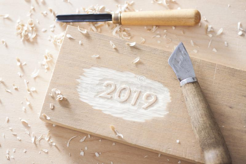 Carved wooden digits 2019 of the New Year on old rustic wooden table. Carved wooden digits forming number 2019 of the New Year on old rustic wooden table royalty free stock photo